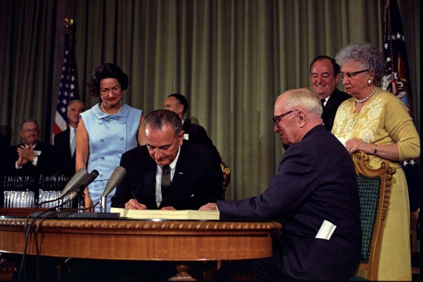 1200px-Lyndon_Johnson_signing_Medicare_bill,_with_Harry_Truman,_July_30,_1965