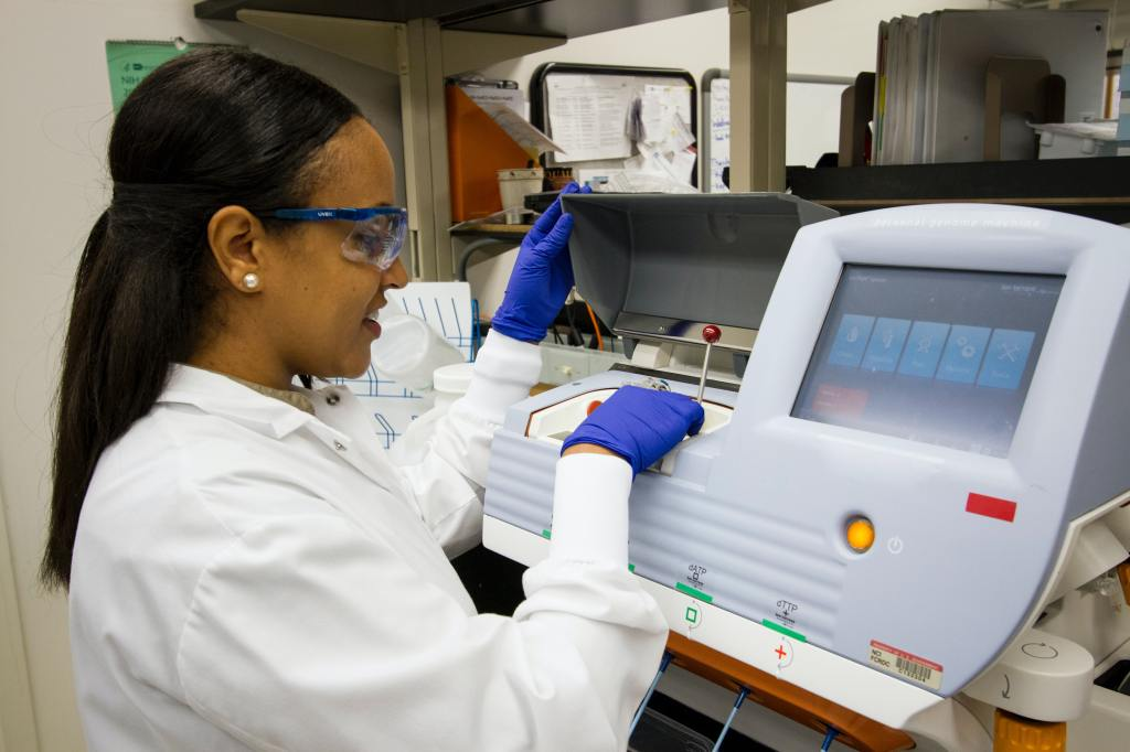 A technician who has long dark hair and is wearing safety glasses, a white coat, and purple gloves, loads DNA samples into a desktop genomic sequencing machine
